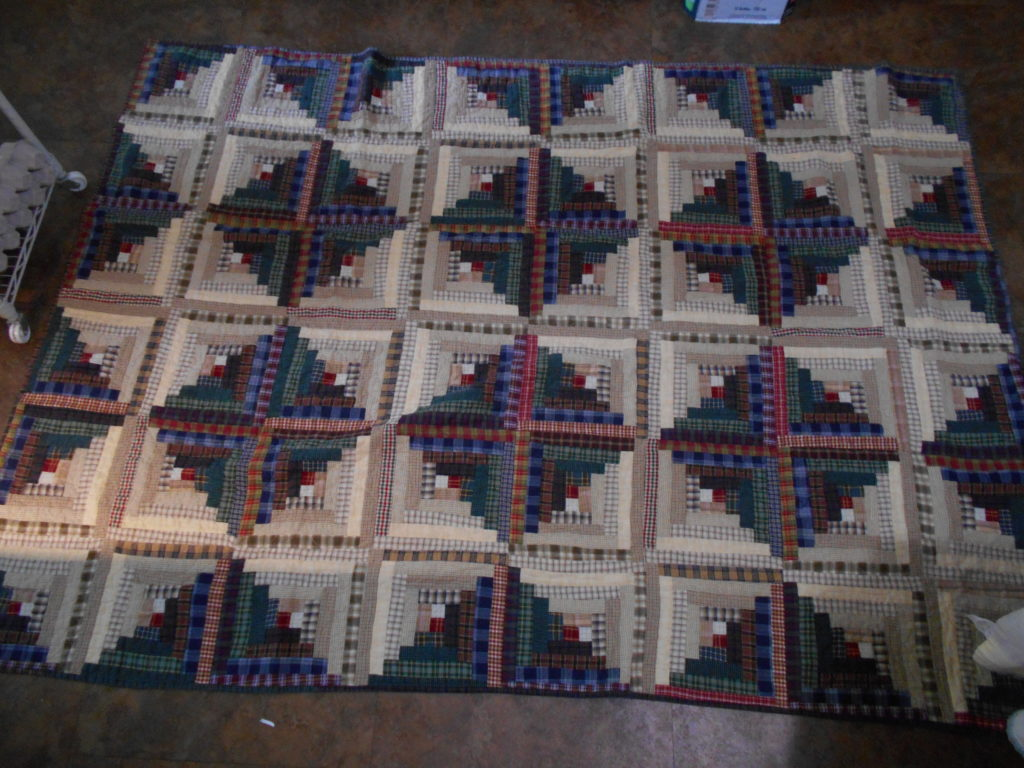 A log cabin quilt set in the Sunshine and Shadows layout, made of plaid fabrics, measuring approximately 4 1/2 x 6 feet.